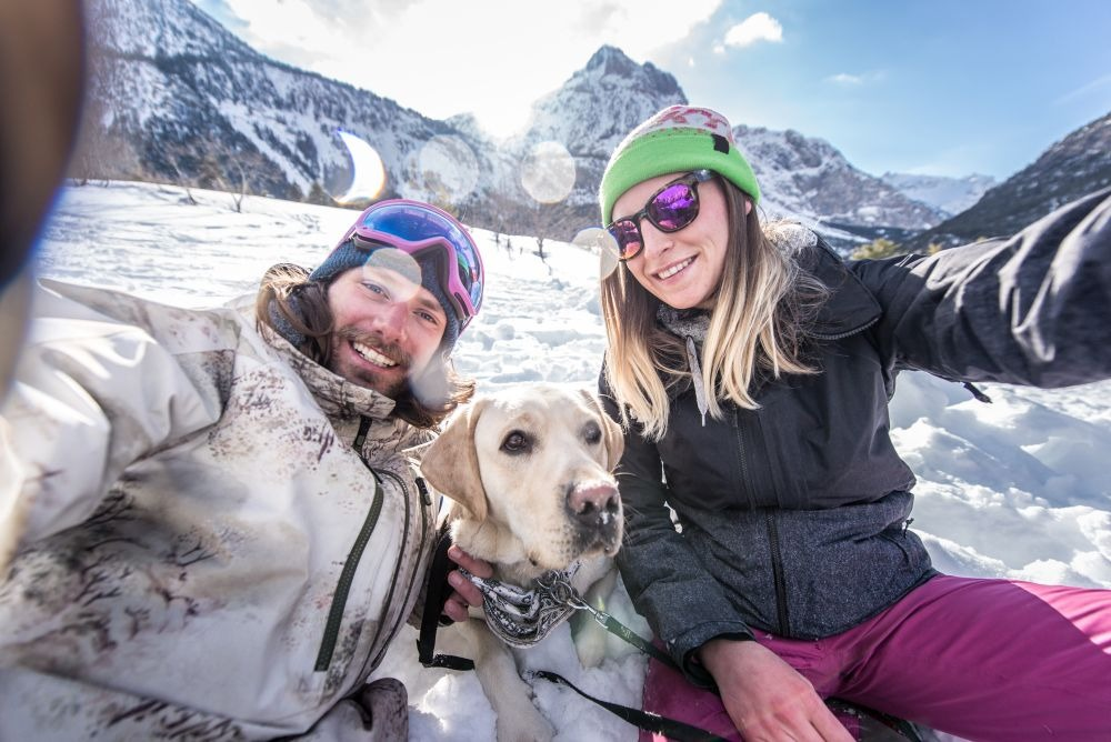 Happy couple playing and having fun with their loyal dog in the snow