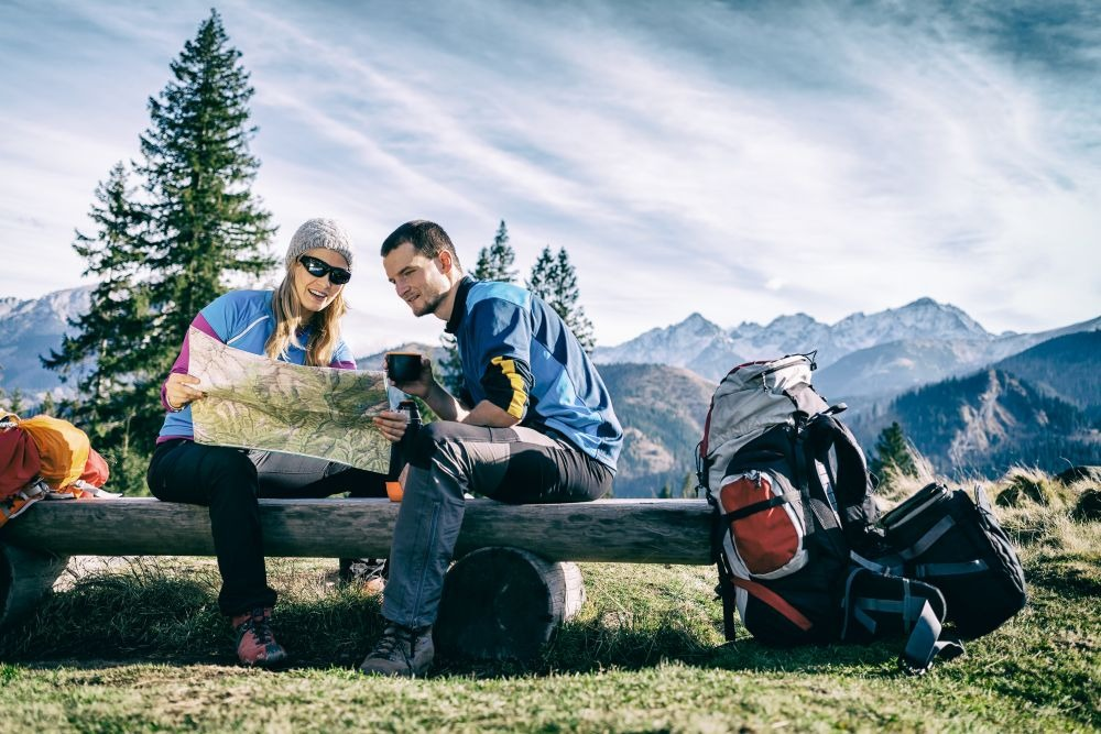 Man and woman hikers hiking in mountains. Young couple camping, looking at map and planning trip or get lost. Getting rest and drinking coffee or tea